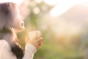 Woman smelling coffee looking peaceful