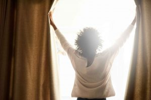 Confident woman opening curtains to the sun